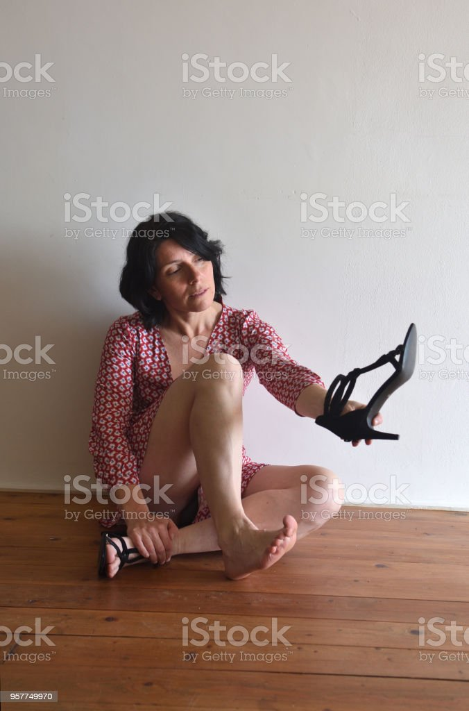 barefoot woman with a shoe in her hand stock photo