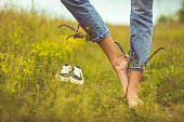 istock Barefoot young woman in idyllic rural field of wildflowers 1243145384