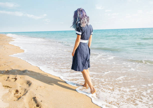 Barefoot young woman walking on shore. stock photo