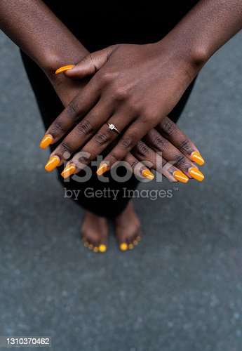 istock Bare-footed black ethnic woman showing her yellow-painted nails and hands on the street 1310370462