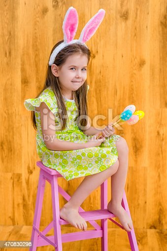 istock Barefooted girl wearing bunny ears, holding bunch of colorful eggs 470830298