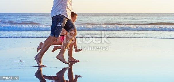 istock Barefooted legs of family running on beach 520296188