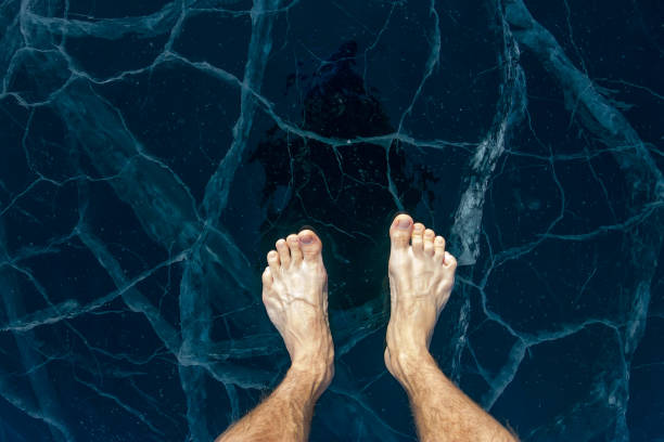 Barefooted male feet stand on the blue ice of Lake Baikal, in cracks stock photo