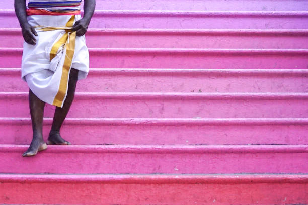 Barefooted man walking down pink color steps Hindu pilgrim walking down pink color staircase with copy space kuala lumpur batu caves stock pictures, royalty-free photos & images