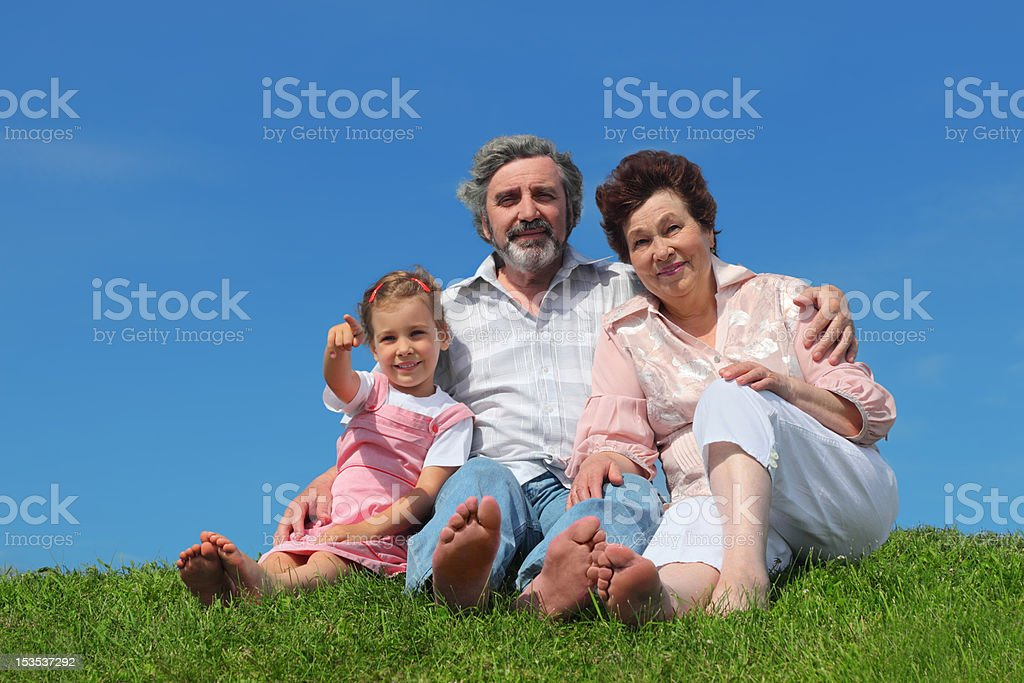 Barefooted old man and woman sitting with granddaughter royalty-free stock photo