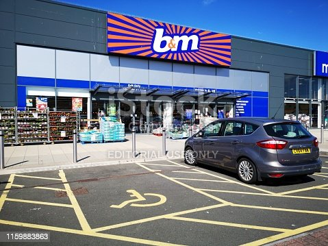 Swansea, UK: July 03, 2019: B&M Bargains retail shop front with merchandise and bargain items displayed outside. Disabled parking is available directly outside the shop.