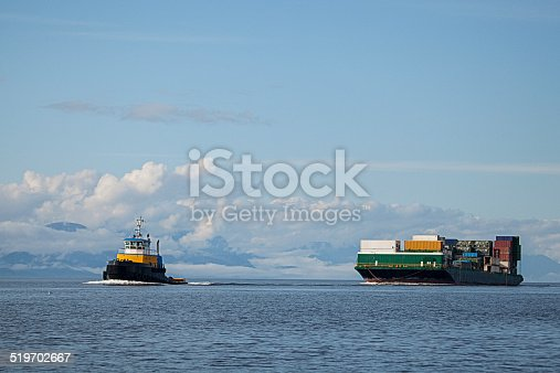 A tug boat leads a barge carrying semi trailers into a harbor in Alaska.
