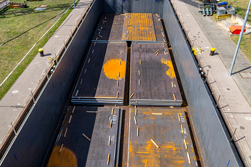 Barge filled with sheets of thick metal, flowing into the river lock, top view of the cargo holds of the ship.