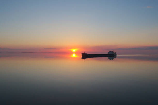 Barge is on the lake at sunset stock photo