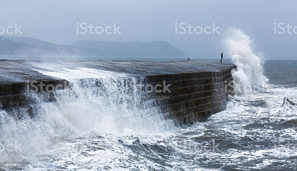 A barge standing strong against rough waves in the ocean stock photo