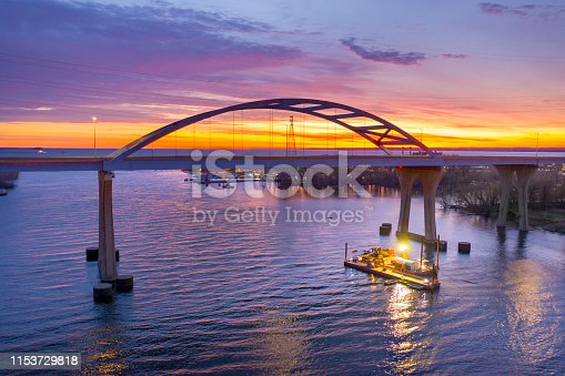 A dredging barge begins a long day of work before sunrise in the morning, under scenic bridge.