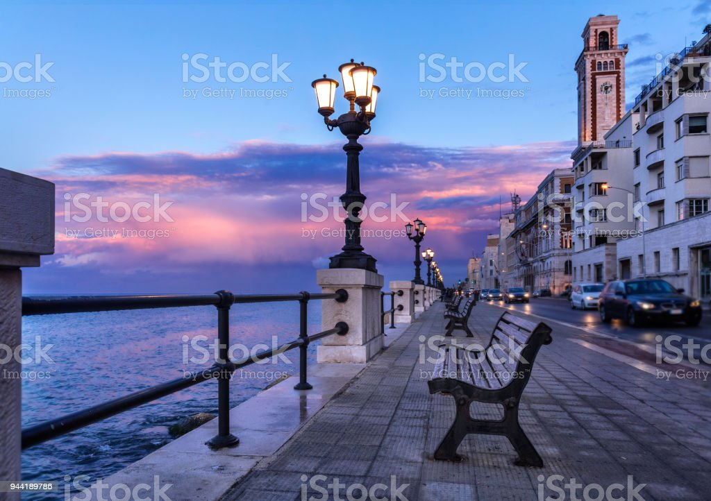 Bari seafront. Colorful amazing sunset. Coastline and cityscape. Twilight purple and blue sky. stock photo
