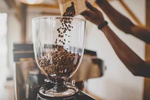 Barista adding beans to grinder bowl