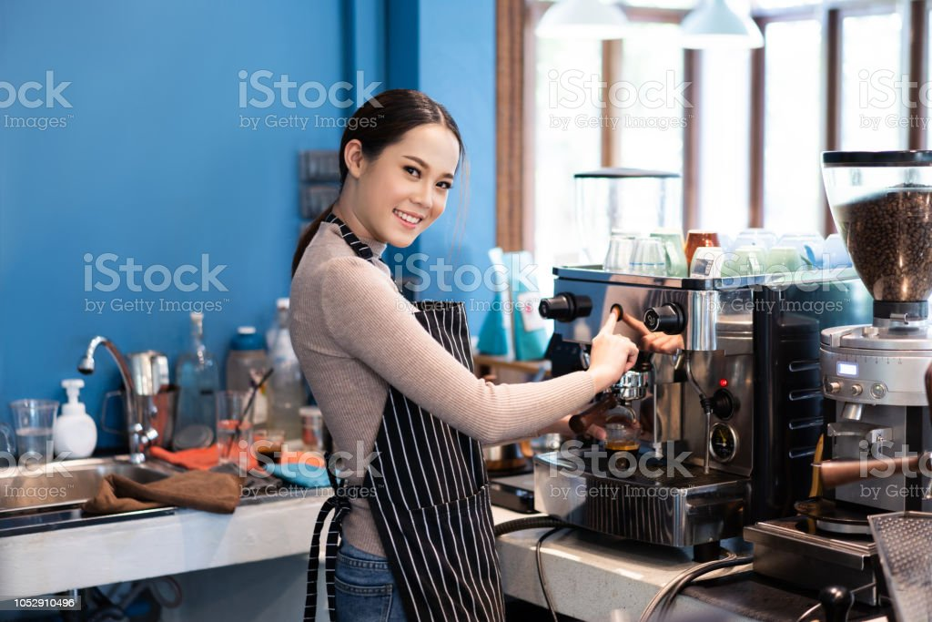Barista asian woman are making coffee in a store owned by a business.