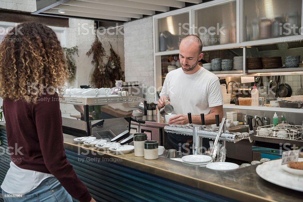 Barista at coffee shop bar making capuccino stock photo