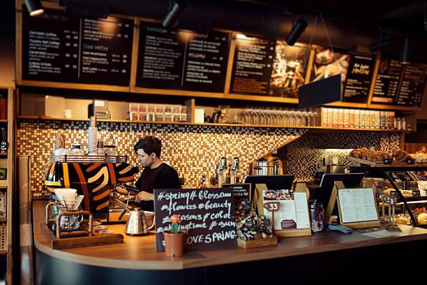 barista at work in a coffee shop - kaffee shop stock-fotos und bilder