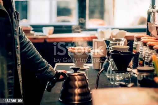 side view of a barista waiting for coffe to be brewed