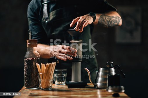 Barista making air press pour over coffee. Barista with tattooed arms wearing dark uniform.