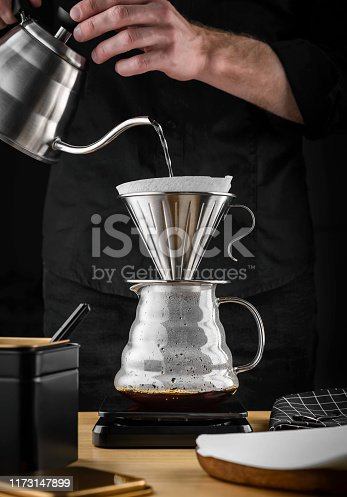 istock A barista brews coffee by an alternative method in pour over, coffee filter, glass teapot on a wooden tray on a dark background. 1173147899