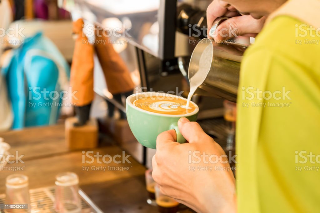 Close up barista hands pouring milk for making latte art or...