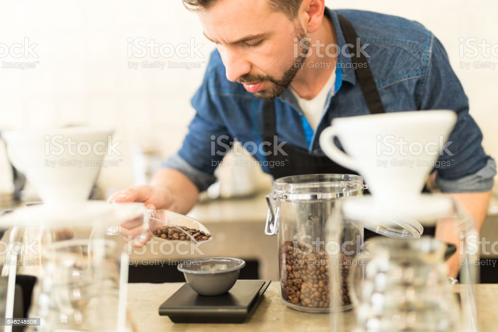 Barista carefully weighing coffee grains stock photo