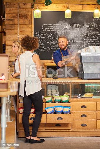 597640822istockphoto Barista chatting with customer 597640558