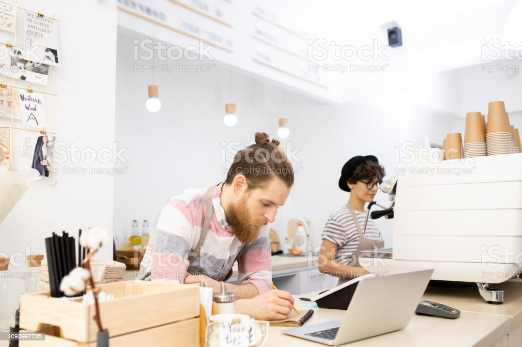 Barista checking orders in notepad stock photo