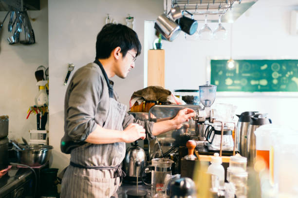 Barista Cleaning and Organizing Coffee Machine at Cafe Counter stock photo