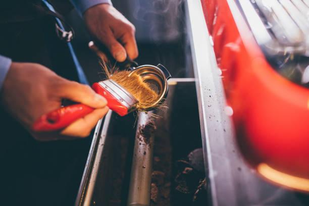 Barista cleaning espresso machine, close up stock photo