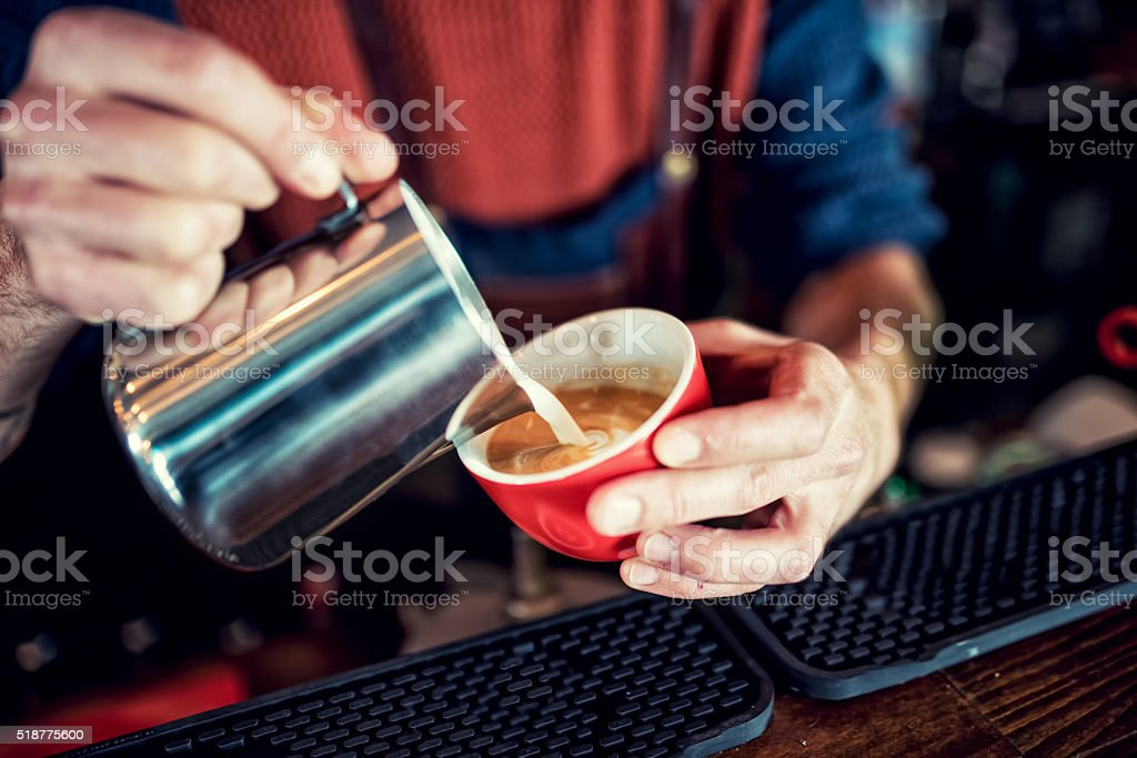 Barista creating latte art on long coffee with milk stock photo