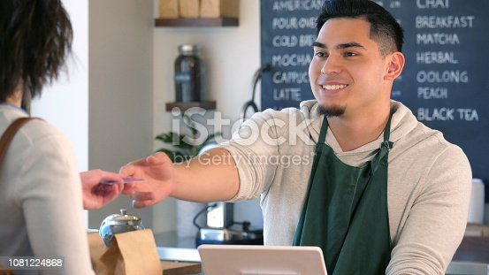 597640822istockphoto Barista hands credit card back to female customer 1081224868