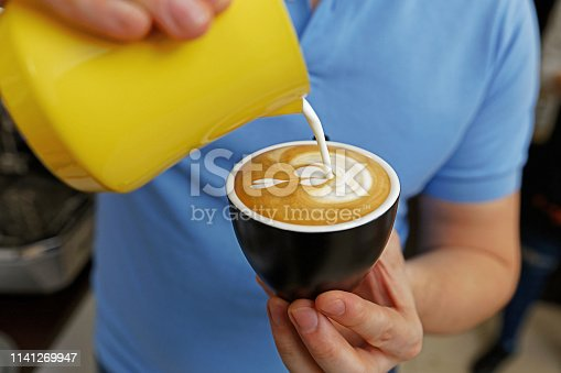 istock Barista holding and pouring milk to milk to make latte art. 1141269947