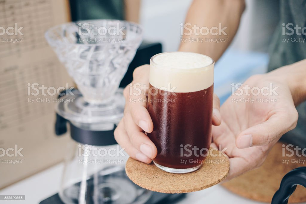 Barista holding and serving a drinking glass of cold brew dip coffee. stock photo
