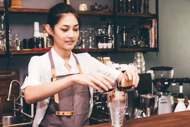barista holding coffee in coffee shop - barista making coffee stock photos and pictures