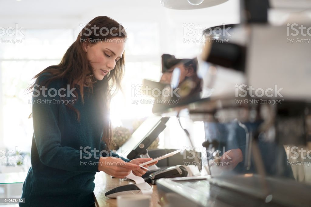 Barista holding digital tablet and bill in cafe stock photo