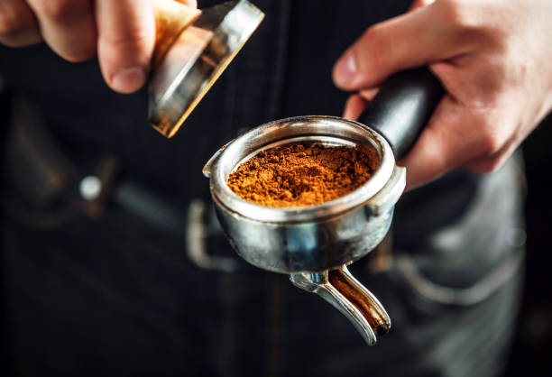Barista holding portafilter and coffee tamper. Barista holding portafilter and coffee tamper making an espresso coffee. barista stock pictures, royalty-free photos & images