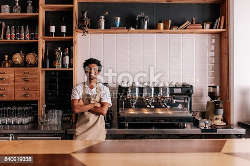 istock Barista in apron looking at camera and smiling 840619338