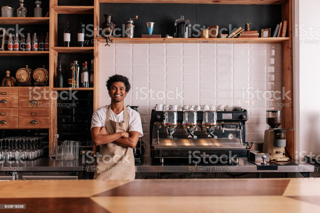 Barista in apron looking at camera and smiling stock photo