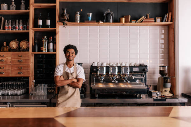 barista in apron looking at camera and smiling - barista stock photos and pictures