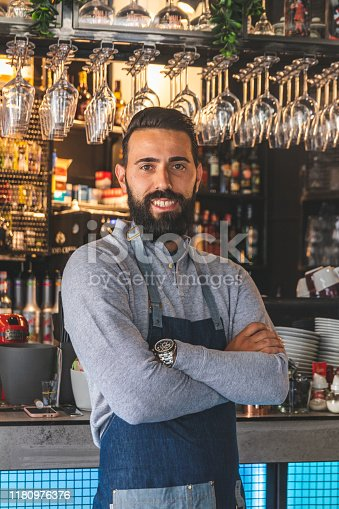 1003493404istockphoto Barista in apron looking at camera and smiling while standing in front of bar counter 1180976376