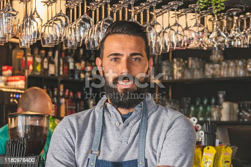 1003493404istockphoto Barista in apron looking at camera and smiling while standing in front of bar counter 1180976400