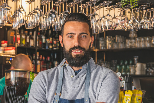 1003493404 istock photo Barista in apron looking at camera and smiling while standing in front of bar counter 1180976400
