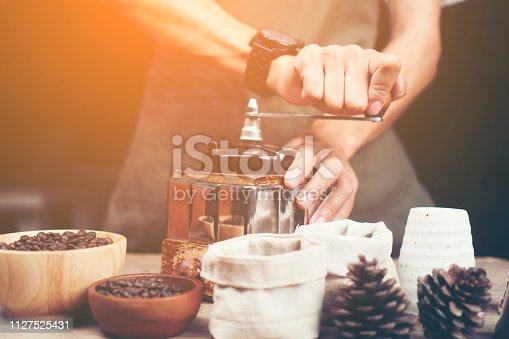 istock Barista is grinding coffee with a hand coffee grinder. 1127525431