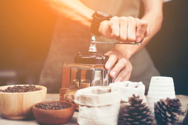 Barista is grinding coffee with a hand coffee grinder. Barista is grinding coffee with a hand coffee grinder. grinding stock pictures, royalty-free photos & images