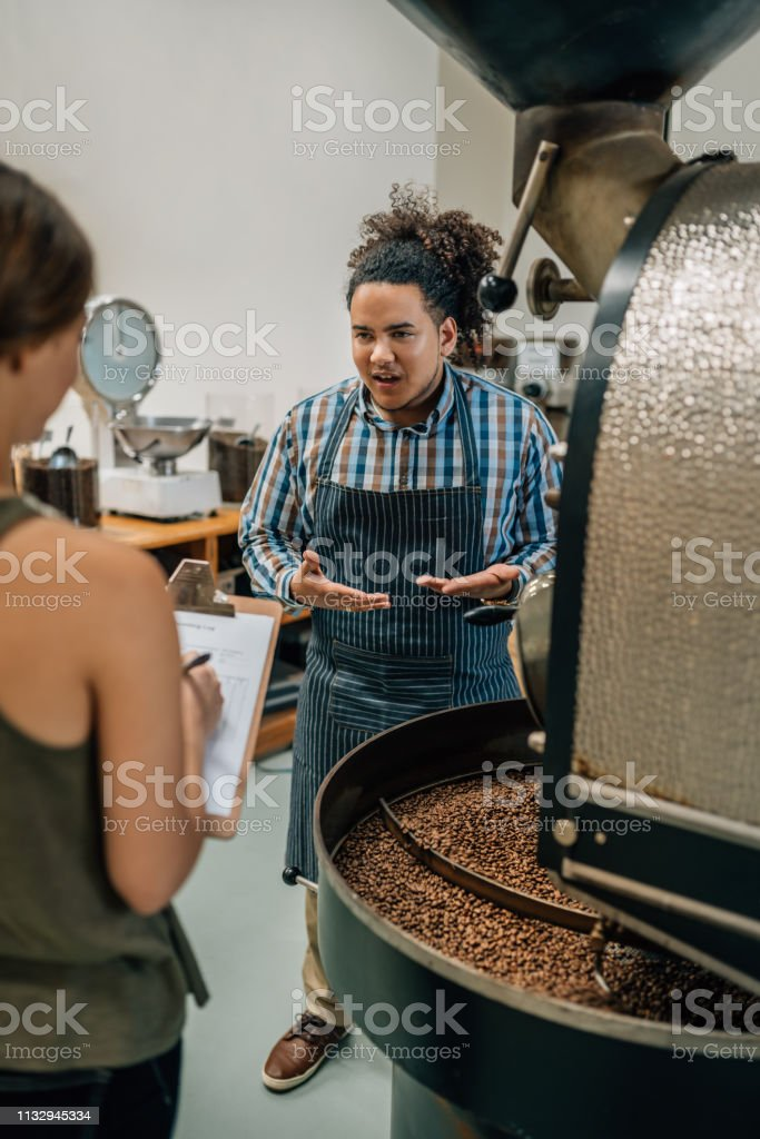 Barista is having the roast of his coffee beans quality checked by...