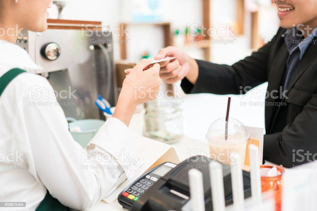 Barista is making coffee at his restaurant. and own a coffee shop she is swiping credit card. Where customers are paying stock photo