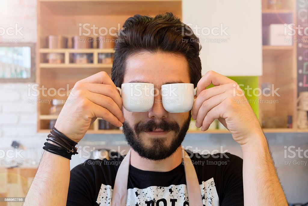 Barista keeps cups of coffee on face - foto de stock