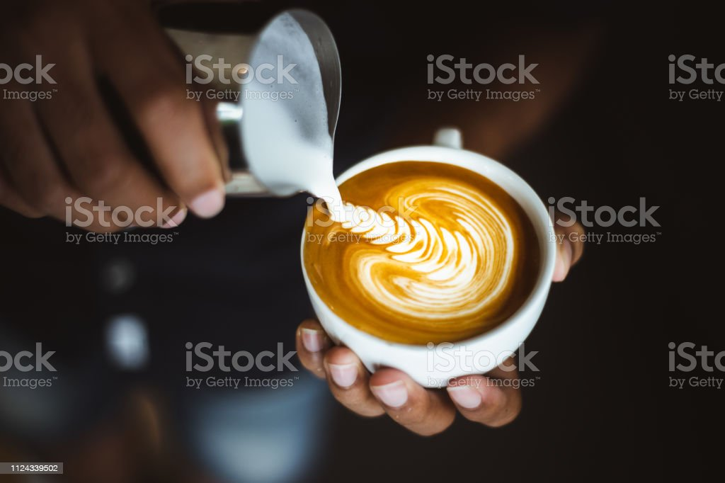 Barista making a cup of coffee latte art in coffee shop.
