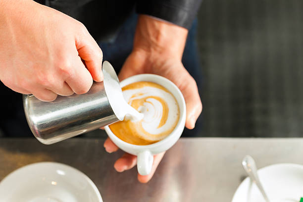 barista making cappuccino in his coffeeshop - barista making coffee stock photos and pictures