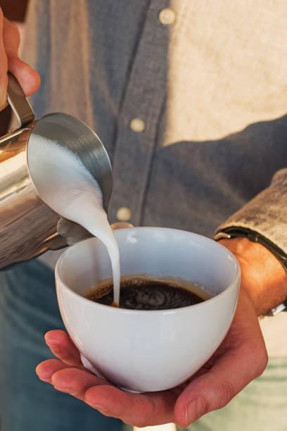 Barista making cappuccino, pouring milk to espresso stock photo